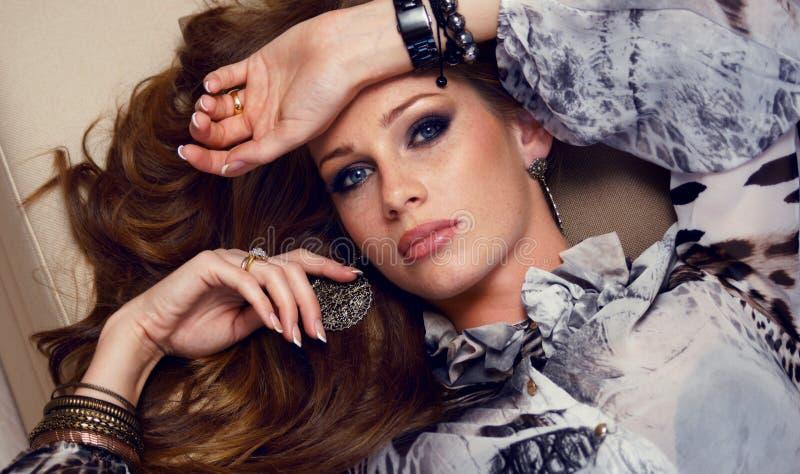 Mulher bonita com o cabelo vermelho que encontra-se no divã imagem de stock royalty free