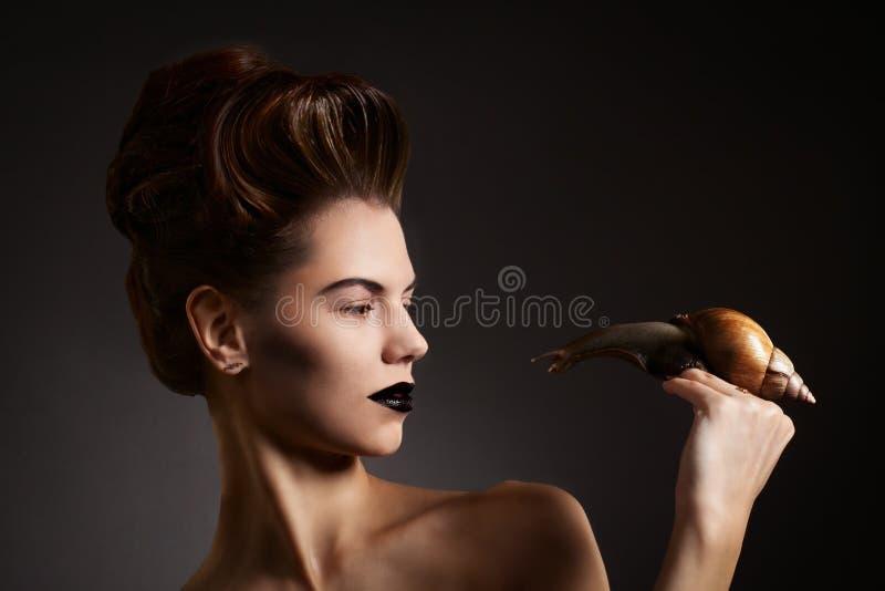 Mulher bonita com o caracol com olhos roxos e bordos. Forma. Vá fotografia de stock royalty free
