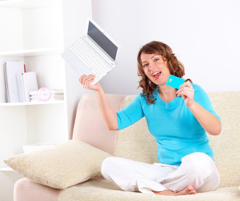 Mulher bonita com o cartão do netbook e de crédito fotografia de stock royalty free