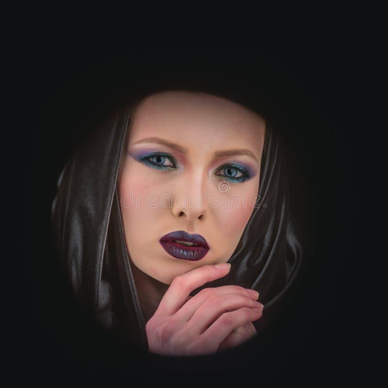 Mulher bonita com o casaco preto sobre o fundo preto imagens de stock royalty free