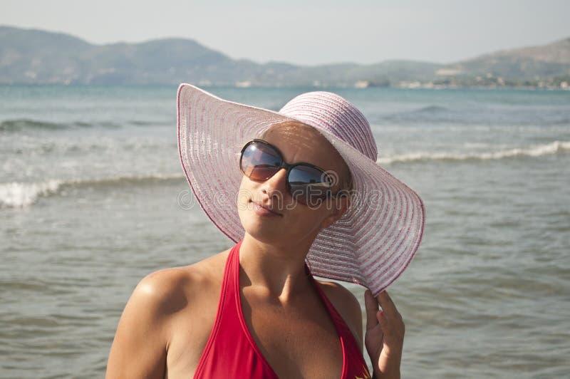 Mulher bonita com o chapéu de palha que levanta perto da praia imagens de stock
