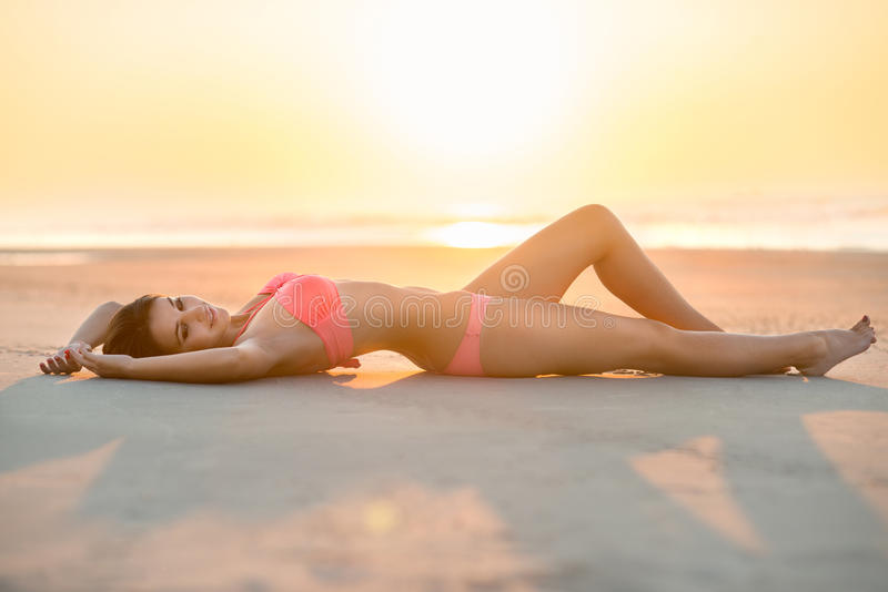 Mulher bonita com o corpo perfeito que encontra-se na praia fotografia de stock royalty free