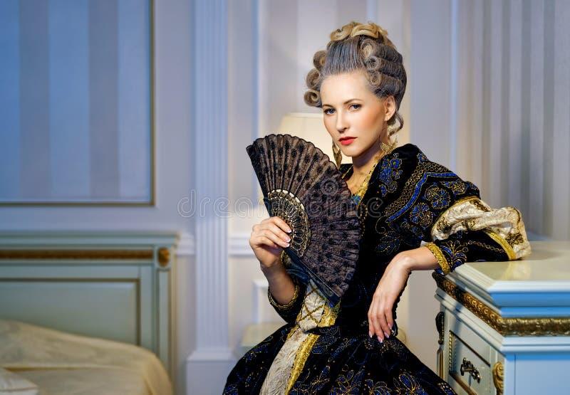Mulher bonita com o fã no vestido histórico no estilo barroco dentro fotografia de stock royalty free