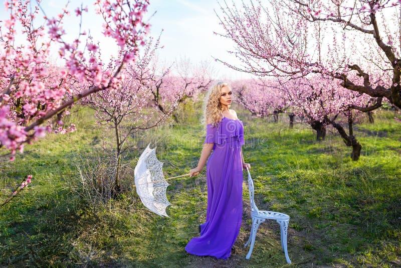Mulher bonita com o guarda-chuva em um dia ensolarado no jardim de florescência, no dia de mola bonito para uma caminhada, na flo imagens de stock