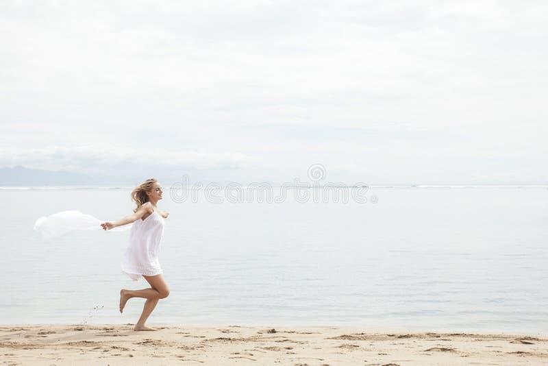 Mulher bonita com o lenço que sente livre na praia foto de stock
