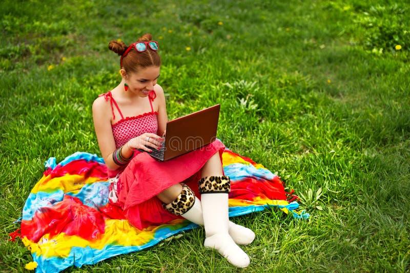 Mulher bonita com o portátil na grama imagem de stock