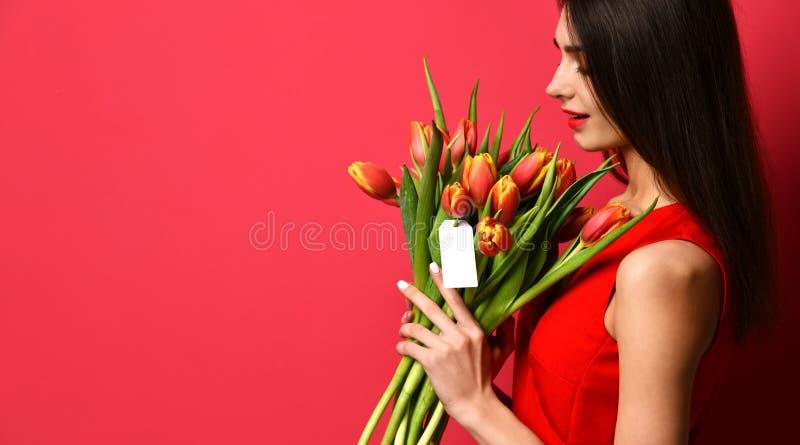 A mulher bonita com o ramalhete da tulipa floresce no vestido vermelho e na pouca etiqueta em tulipas com espaço vazio livre do t fotos de stock royalty free