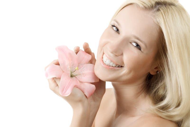 Mulher bonita com o sorriso cor-de-rosa do lírio isolado imagem de stock royalty free