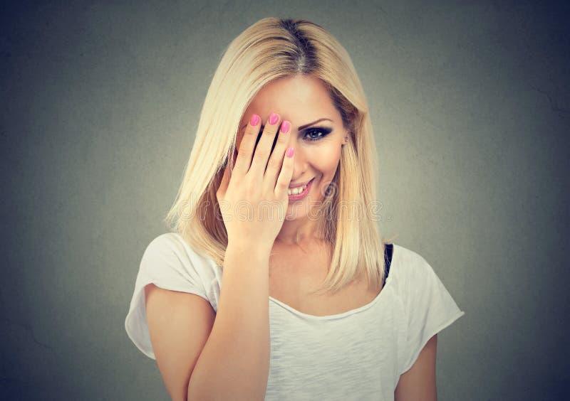 Mulher bonita com o t-shirt branco vestindo longo do cabelo louro, olhando tímido com mão na cara e no sorriso foto de stock royalty free