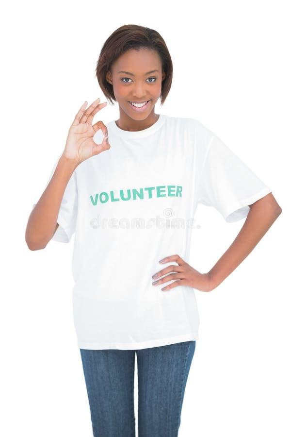 Mulher bonita com o tshirt voluntário que faz o gesto aprovado fotografia de stock royalty free