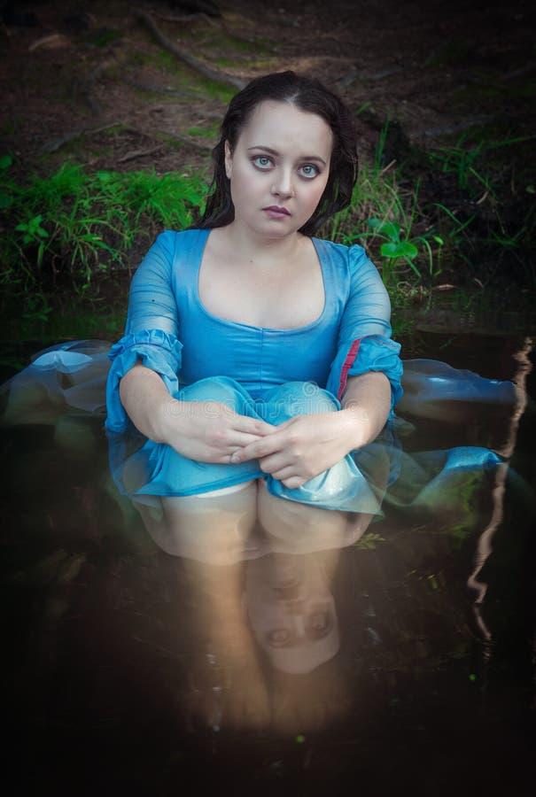 Mulher bonita com o vestido medieval que senta-se na água exterior fotografia de stock royalty free