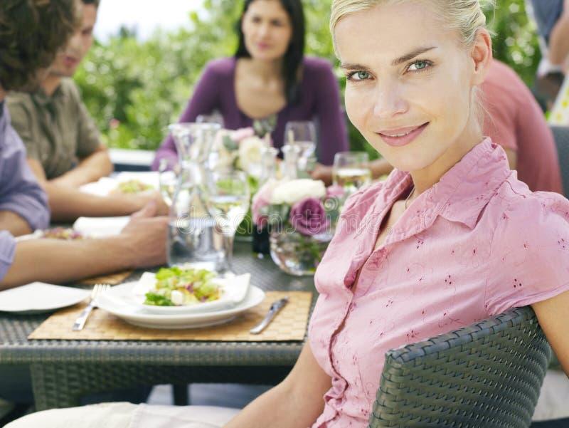 Mulher bonita com os amigos que têm a refeição fora foto de stock