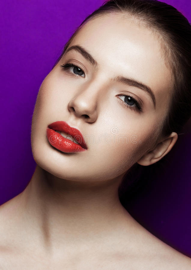 Mulher bonita com os bordos vermelhos da composição no fundo roxo fotografia de stock
