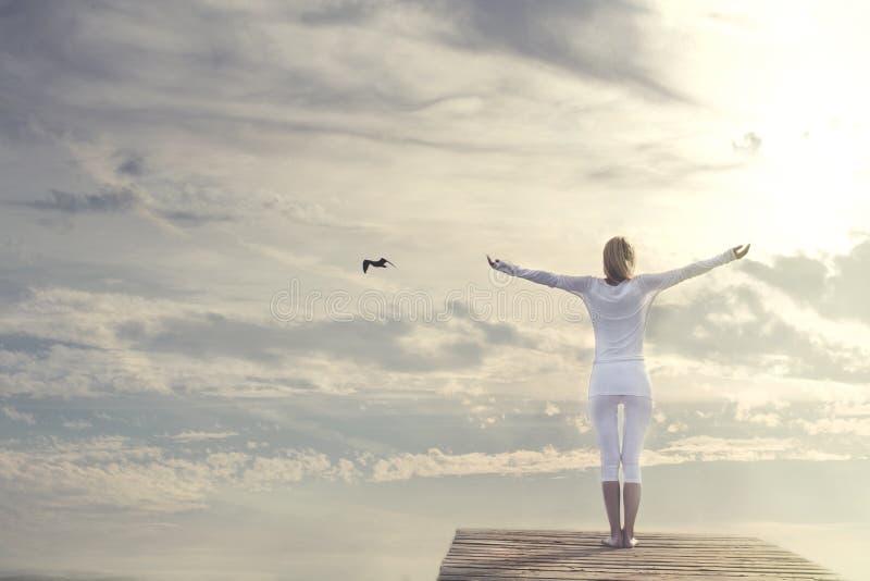 Mulher bonita com os braços abertos que meditam na frente de um céu espetacular fotografia de stock