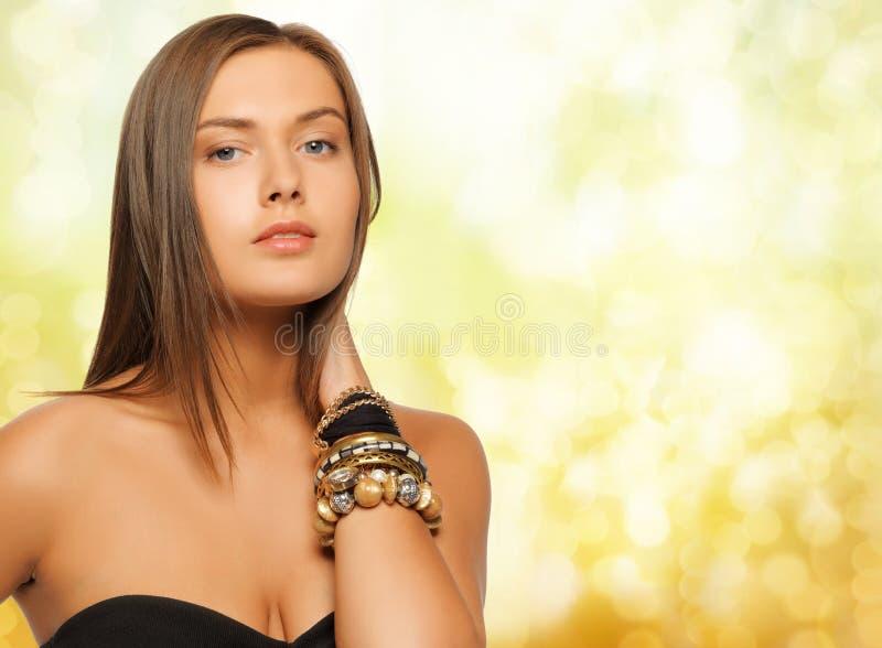 Mulher bonita com os braceletes sobre luzes amarelas fotos de stock royalty free