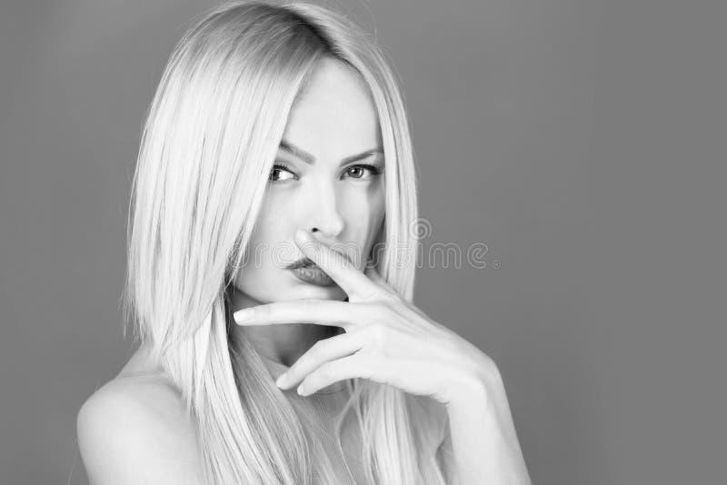 Mulher bonita com os dedos nos bordos 'sexy' na cara pensativa fotos de stock royalty free