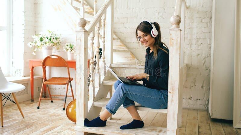 Mulher bonita com os fones de ouvido e o portátil que levantam e que sorriem ao sentar-se em escadas em casa imagem de stock royalty free