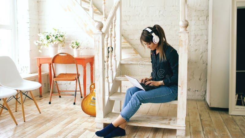 Mulher bonita com os fones de ouvido e o portátil que levantam e que sorriem ao sentar-se em escadas em casa fotografia de stock