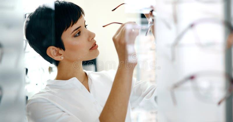 Mulher bonita com os monóculos de tentativa do ótico fotos de stock
