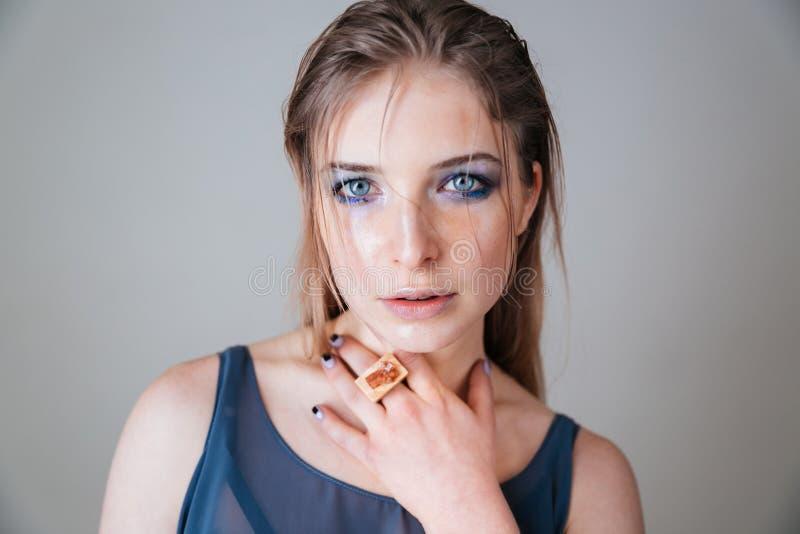 Mulher bonita com os olhos azuis que olham a câmera imagem de stock