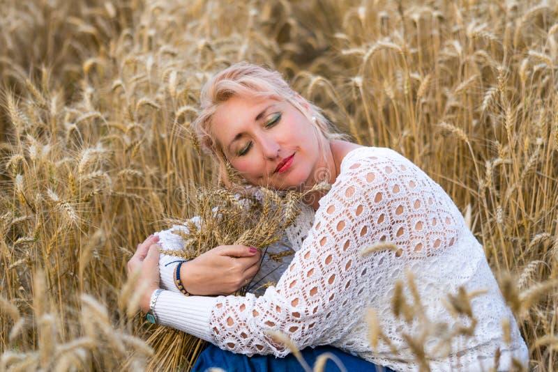 Mulher bonita com os olhos fechados que sentam-se no campo de trigo e no grupo dourados do abraço das orelhas do trigo Liberdade, fotografia de stock royalty free