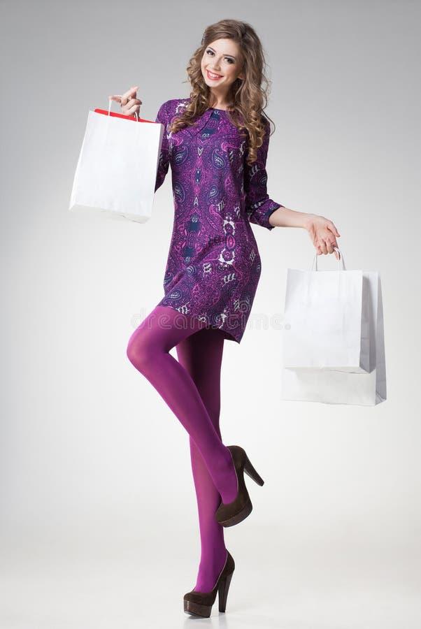 Mulher bonita com os pés 'sexy' longos que guardam sacos de compras foto de stock royalty free