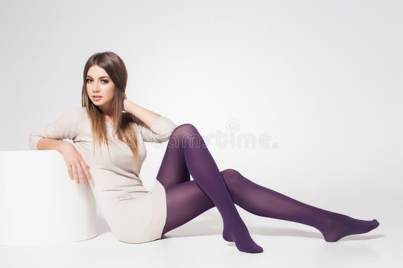 Mulher bonita com os pés 'sexy' longos que vestem as meias que levantam no estúdio - corpo completo fotos de stock