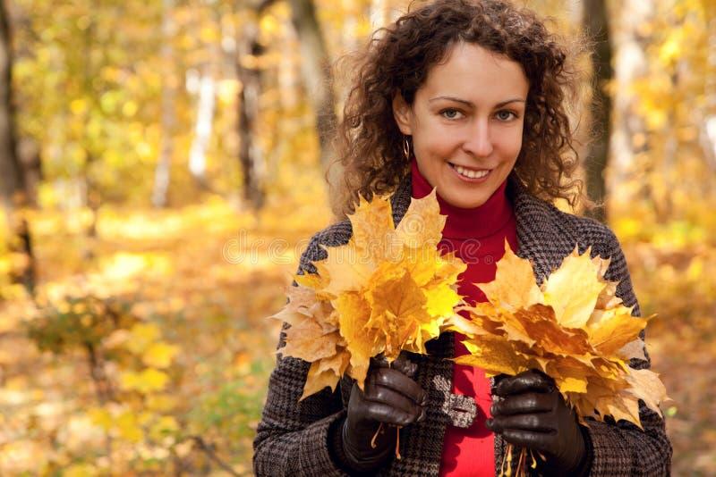 Mulher bonita com os ramalhetes das folhas no parque fotografia de stock