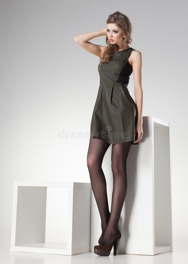 Mulher bonita com pés 'sexy' longos no vestido de couro que levanta no estúdio - corpo completo imagens de stock