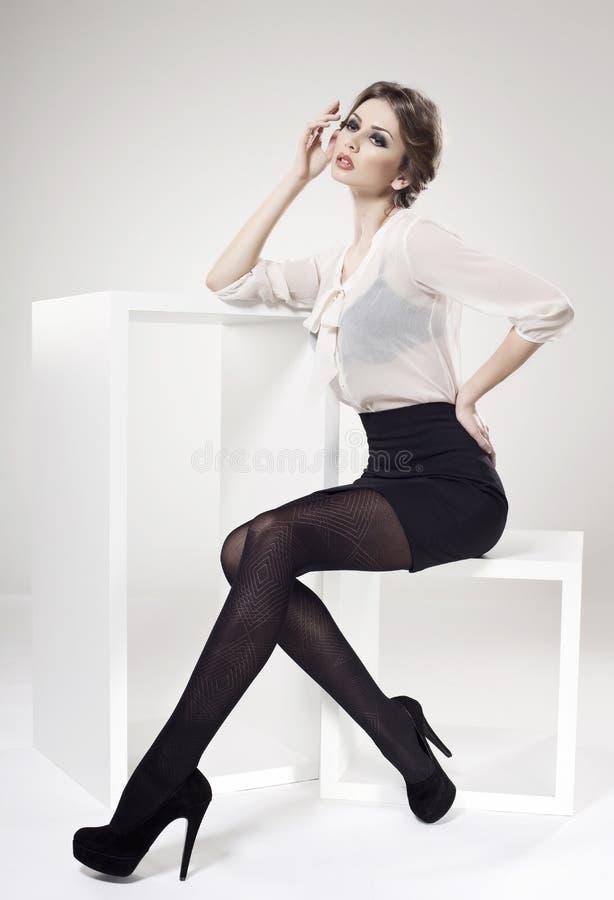 A mulher bonita com pés 'sexy' longos vestiu elegante imagem de stock