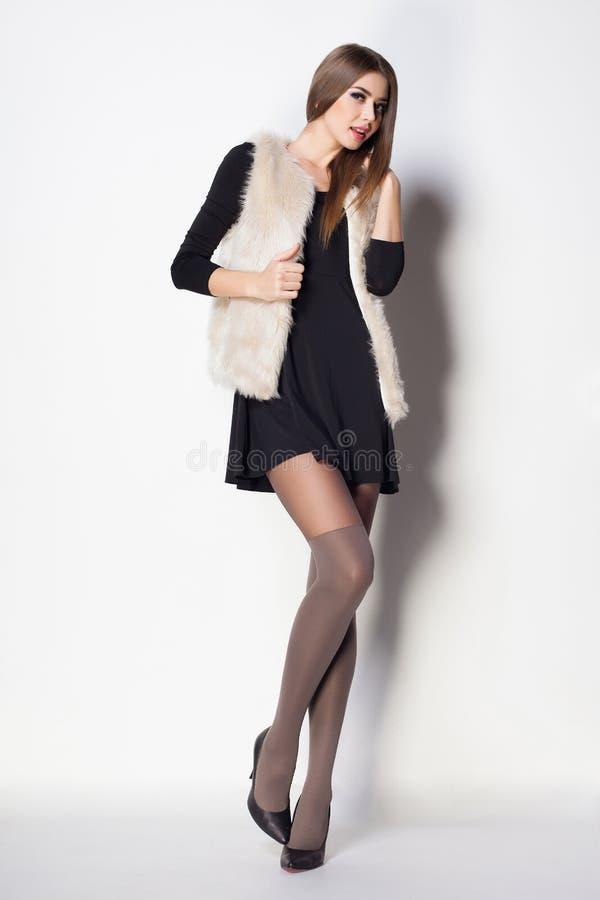 A mulher bonita com pés 'sexy' longos vestiu o levantamento elegante fotografia de stock royalty free