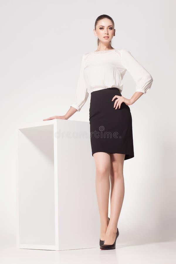 A mulher bonita com pés 'sexy' longos vestiu o levantamento elegante no estúdio foto de stock royalty free