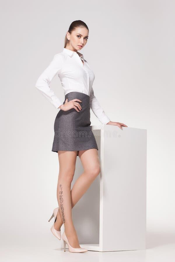 A mulher bonita com pés 'sexy' longos vestiu o levantamento elegante no estúdio fotografia de stock royalty free
