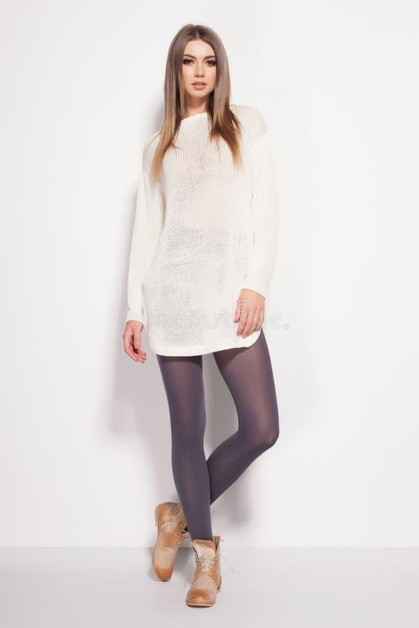A mulher bonita com pés 'sexy' longos vestiu o levantamento elegante no estúdio imagens de stock