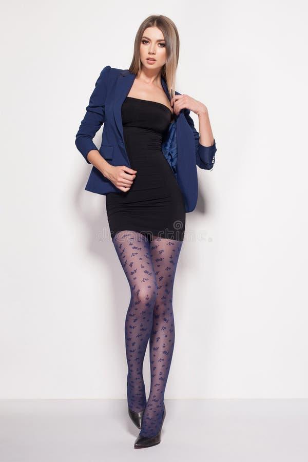 A mulher bonita com pés 'sexy' longos vestiu o levantamento elegante no estúdio fotografia de stock