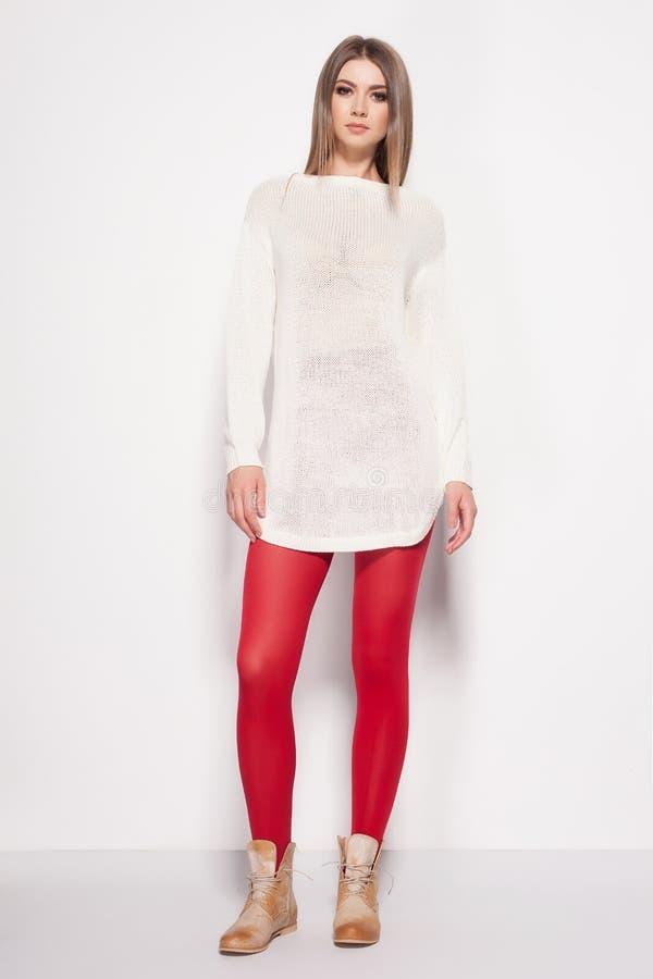 A mulher bonita com pés 'sexy' longos vestiu o levantamento elegante no estúdio fotos de stock