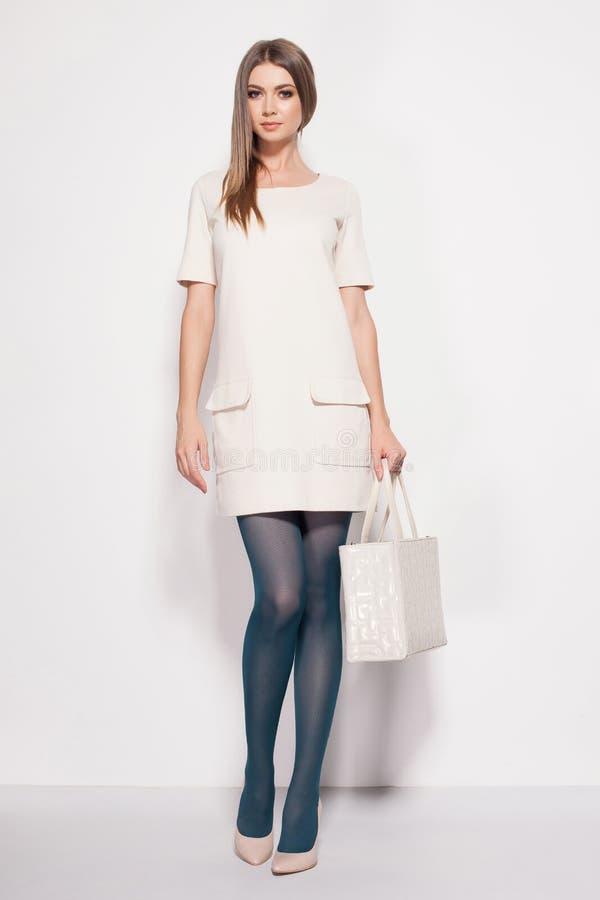 A mulher bonita com pés 'sexy' longos vestiu o levantamento elegante no estúdio imagem de stock