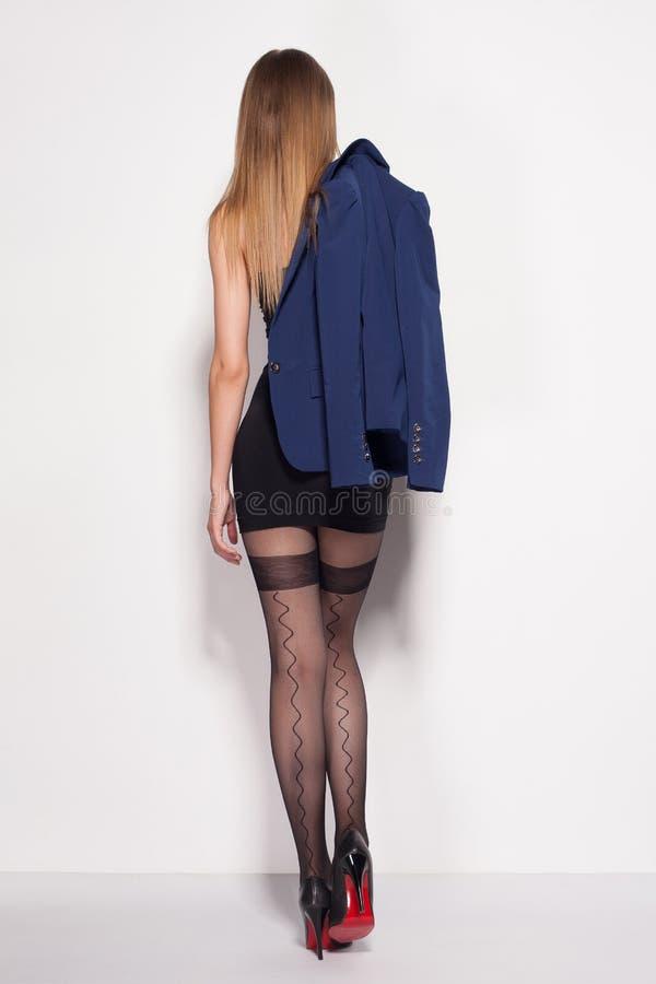A mulher bonita com pés 'sexy' longos vestiu o levantamento elegante no estúdio imagens de stock royalty free