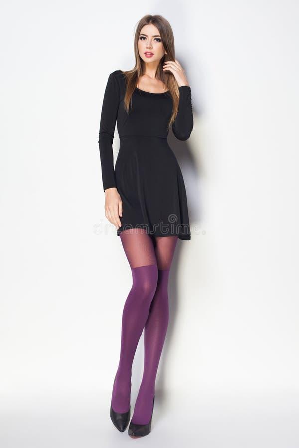 A mulher bonita com pés 'sexy' longos vestiu o levantamento elegante no th fotografia de stock royalty free