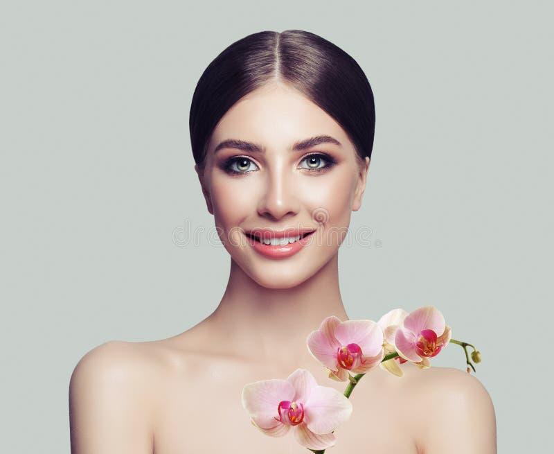 A mulher bonita com pele saudável e a orquídea cor-de-rosa floresce fotografia de stock