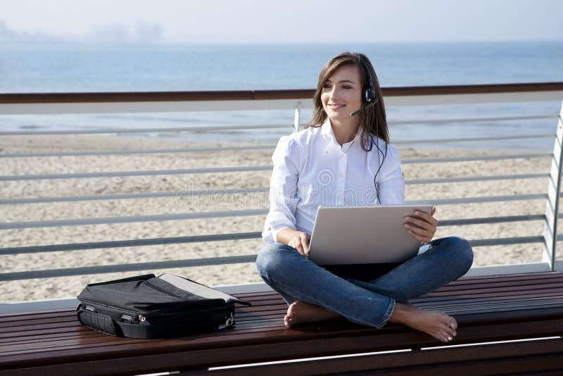 Mulher bonita com portátil e auriculares pelo mar foto de stock royalty free