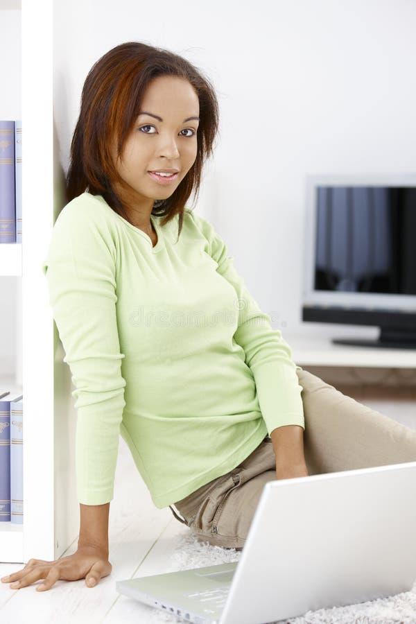 Mulher bonita com portátil em casa foto de stock royalty free