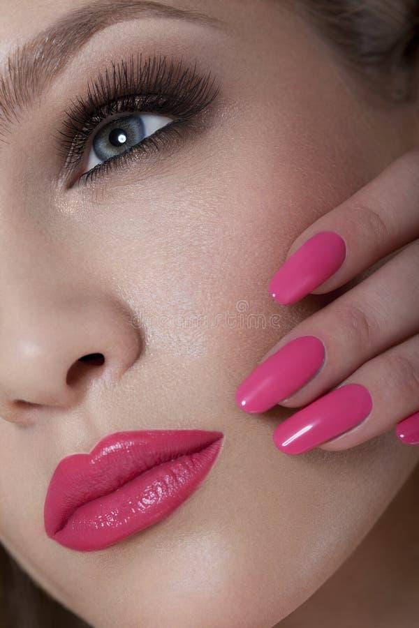 Mulher bonita com pregos cor-de-rosa e composição luxuosa. Bordos 'sexy' vermelhos e pestanas longas fotos de stock
