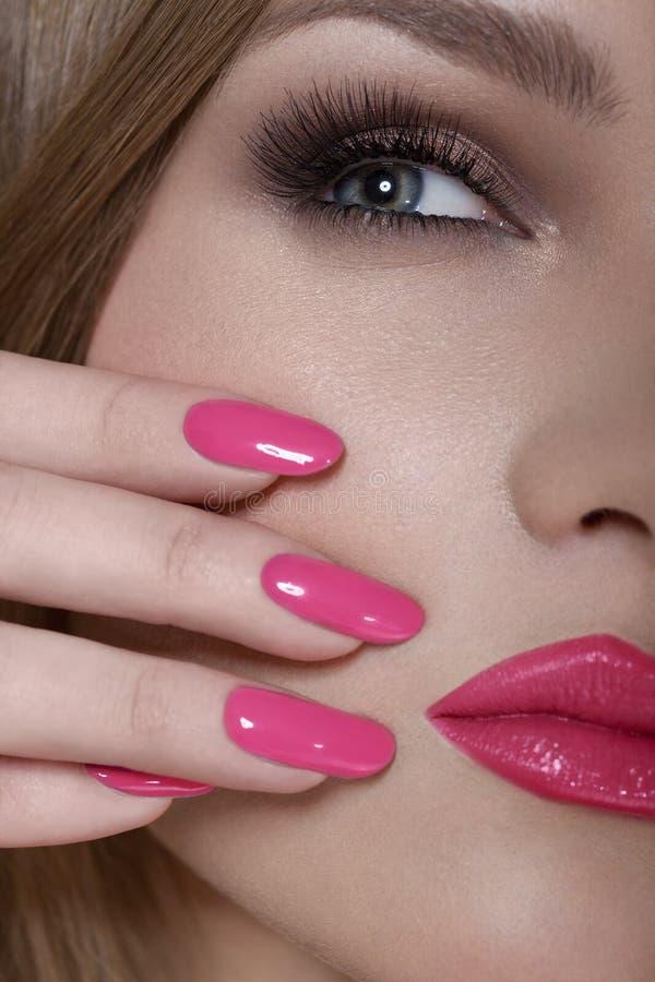 Mulher bonita com pregos cor-de-rosa e composição luxuosa. Bordos 'sexy' vermelhos e pestanas longas imagem de stock