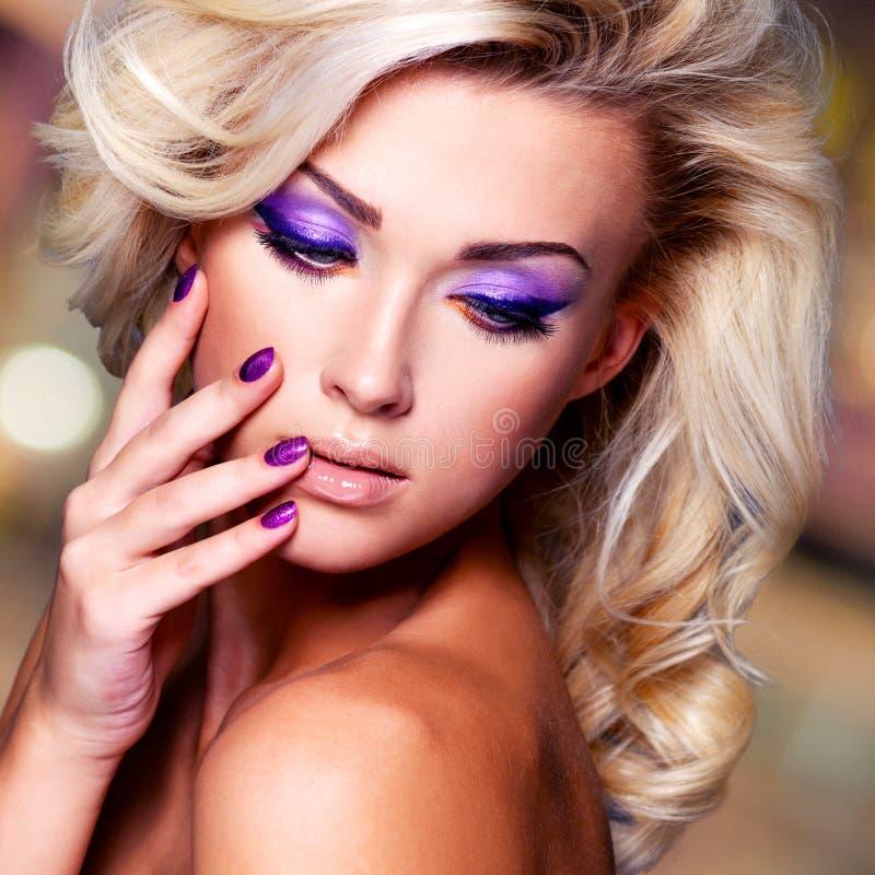 Mulher bonita com pregos roxos e composição do encanto fotos de stock