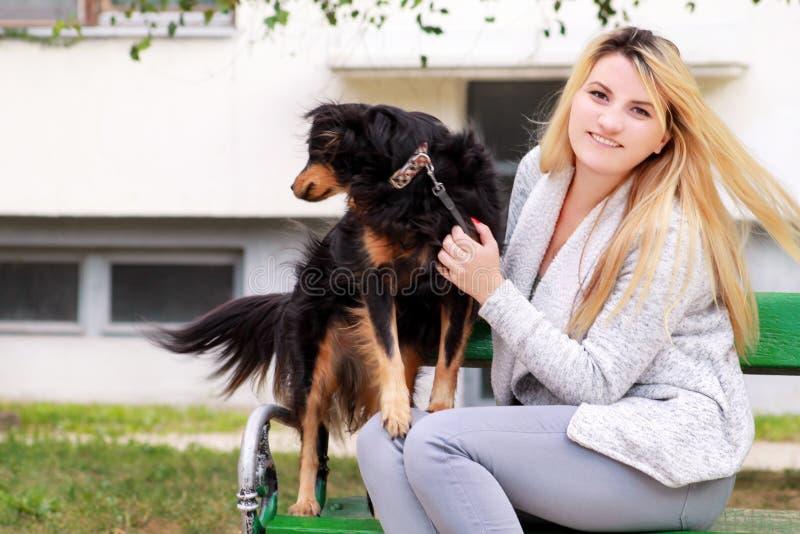 Mulher bonita com seu cão misturado pequeno da raça que senta-se e que levanta na frente da câmera no banco de madeira no parque  fotos de stock royalty free