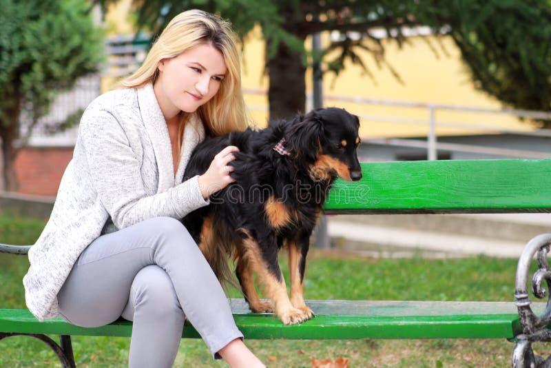 Mulher bonita com seu cão misturado pequeno da raça que senta-se e que levanta na frente da câmera no banco de madeira no parque  fotografia de stock