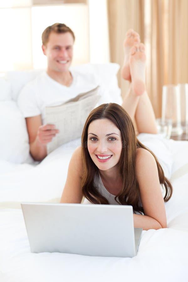 Download Mulher Bonita Com Seu Marido Que Trabalha Em Um Portátil Foto de Stock - Imagem de feliz, lazer: 12813422