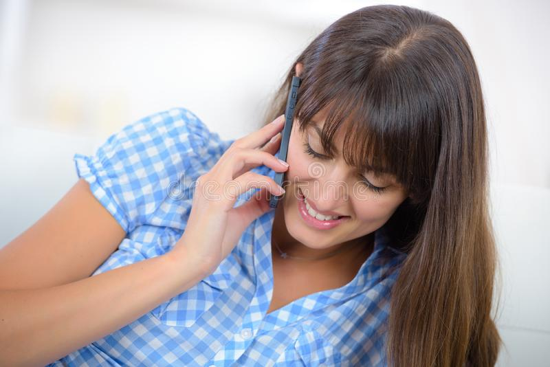 Mulher bonita com telefone em casa fotos de stock