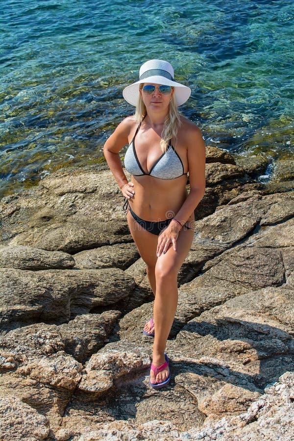 Mulher bonita com um chapéu que relaxa no mar foto de stock